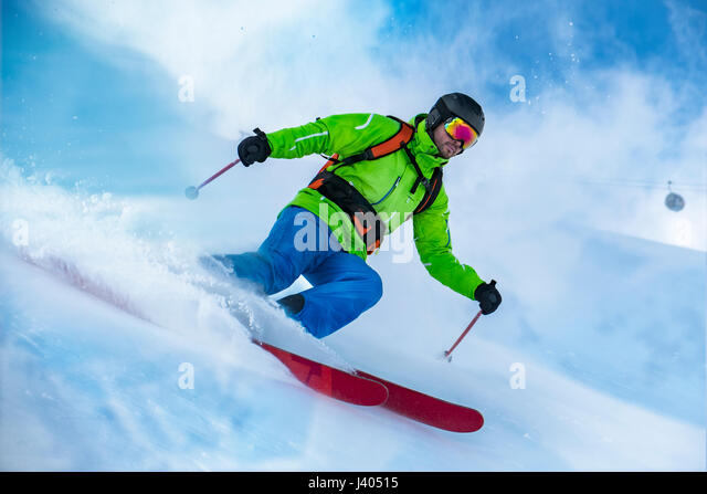 Striking shot of a colorful clothed freerider skiing the snow wave. - Stock-Bilder