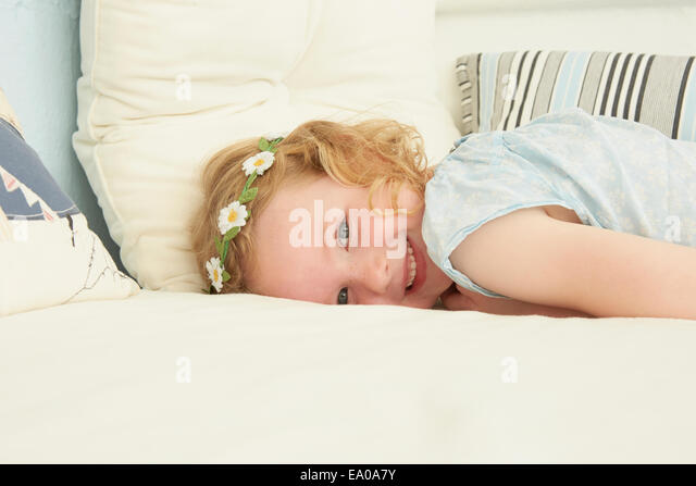 Portrait of girl lying on seat in holiday apartment - Stock Image