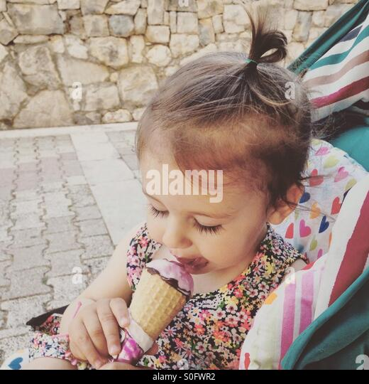 Baby girl eating ice cream outdoor - Stock Image