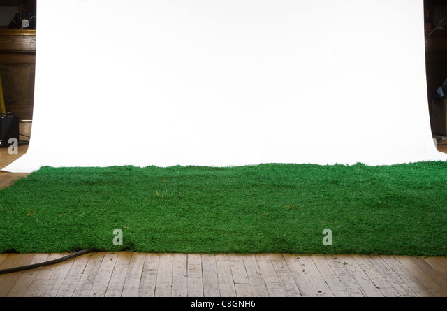 Artificial grass on a wooden floor with a hanging backdrop - Stock Image