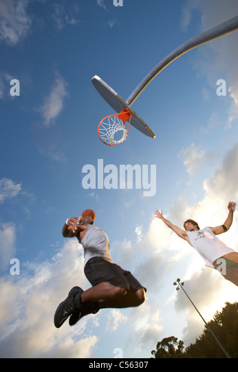 male scoring during outdoor basketball game, upward angle toward goal - Stock Image