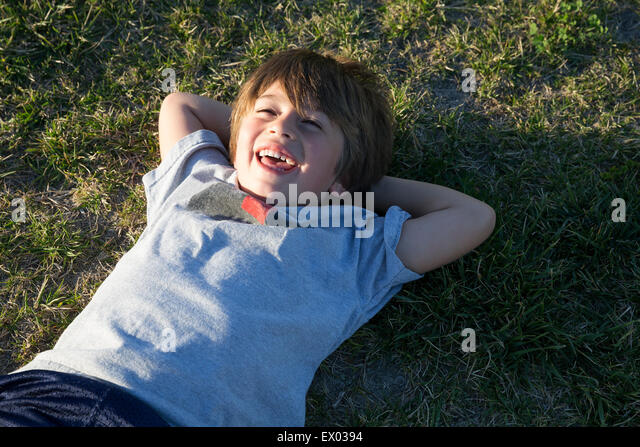 Portrait of boy lying on park grass and laughing - Stock Image