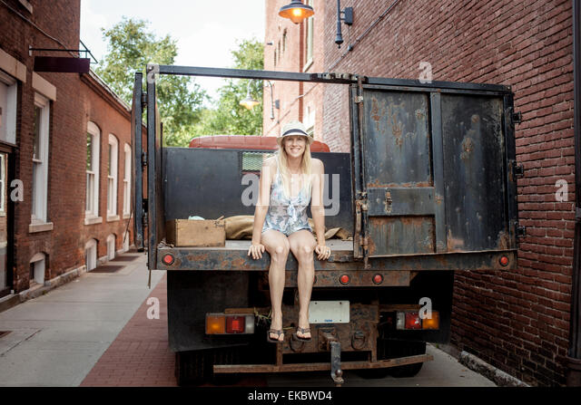 Woman sitting on a farmer's organic food truck outside grocery store - Stock Image