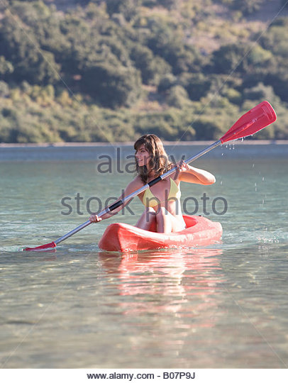 A woman canoeing on a lake - Stock Image