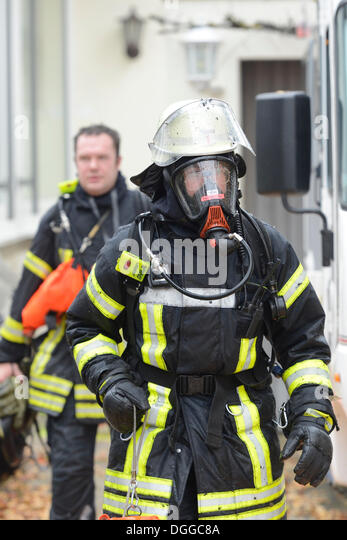 Firefighter wearing breathing equipment during a roof fire, Aichwald, Baden-Wuerttemberg - Stock Image