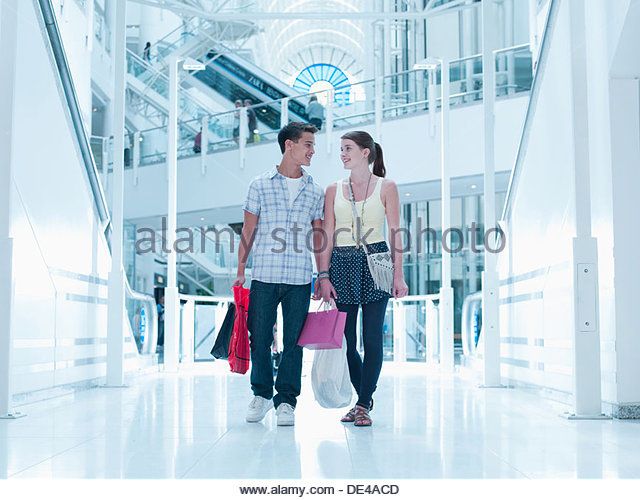 Smiling couple carrying shopping bags in mall - Stock Image
