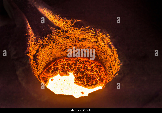 Molten metal in flask in foundry - Stock Image