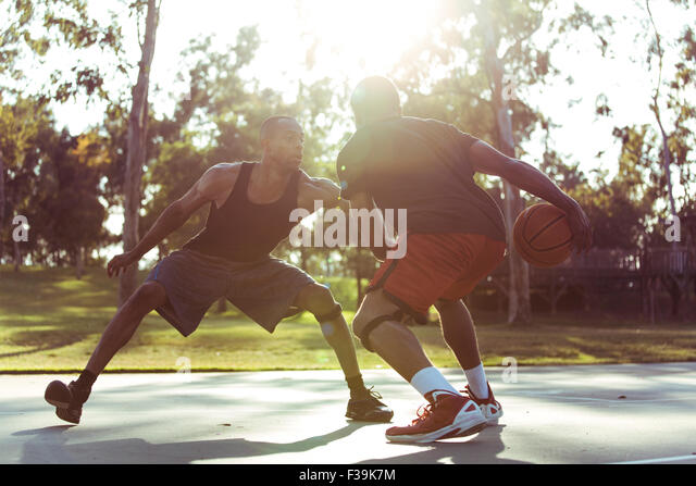 Two young men playing basketball in the park at sunset - Stock Image