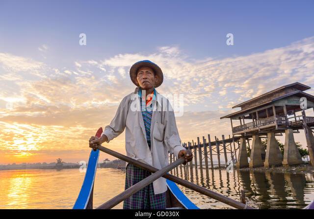 MANDALAY, MYANMAR - OCTOBER 28, 2015: A Gondolier paddles on Taungthaman Lake at U-Bein Bridge. - Stock-Bilder