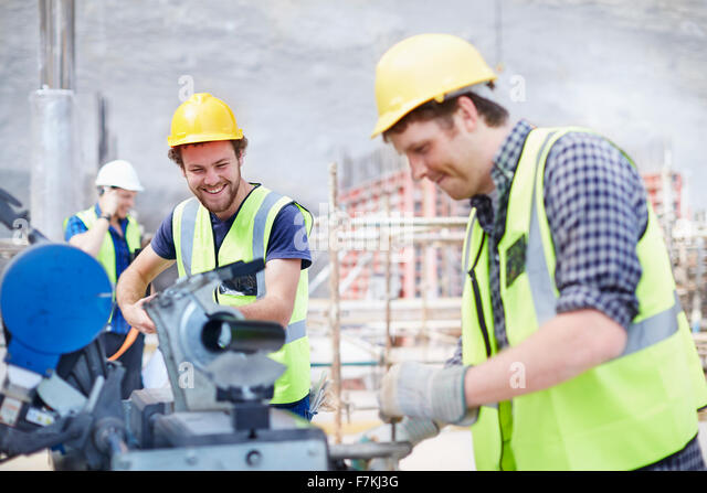 Construction workers using equipment at construction site - Stock Image