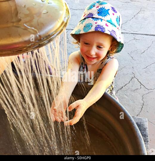 Happy toddler washing her hands - Stock Image