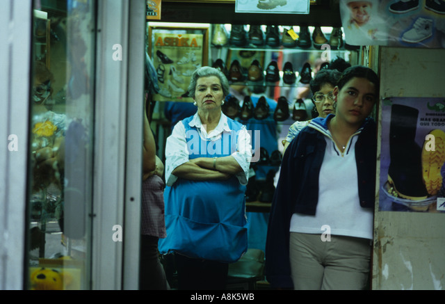 Tired and bored workers look out from a shop in Panama City, Panama during the evening. - Stock-Bilder