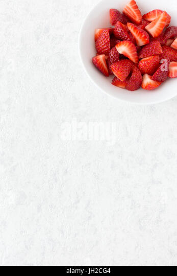 Cut strawberries in a white porcelain bowl isolated on white marble background with lots of copy space. - Stock Image