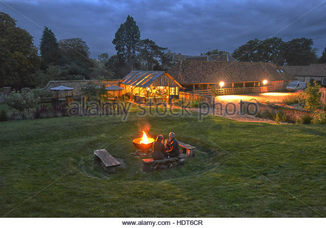 Mature husband and wife drinking wine by campfire. - Stock Image