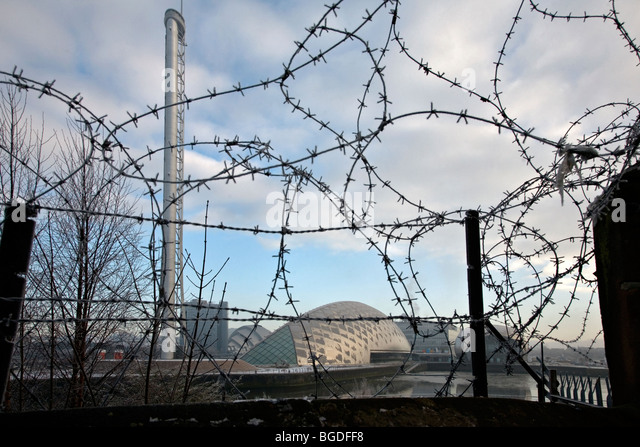 the science centre at Pacific Quay in glasgow seen through barbed wire - Stock Image