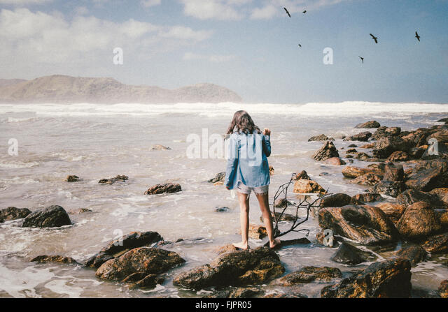 Full Length Rear View Of Woman Standing On Rock At Seaside - Stock Image