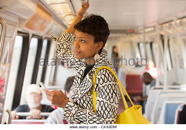 Black woman riding train and holding cell phone - Stock Image