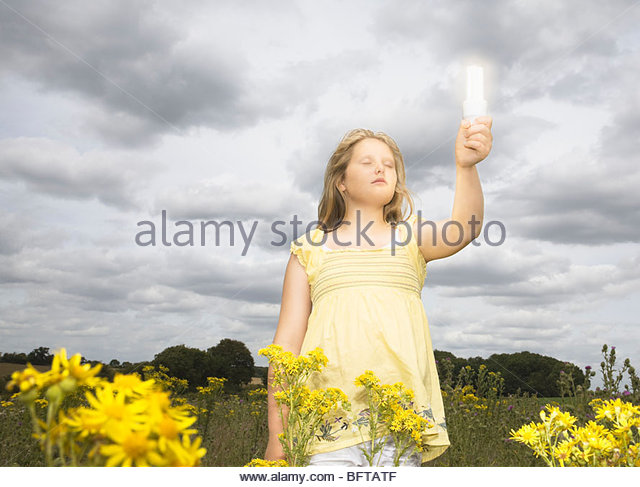 Girl with energy saver bulb in field - Stock Image