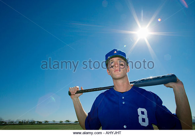 Baseball player, in blue uniform and cap, standing on pitch with bat behind head, front view, portrait lens flare - Stock Image