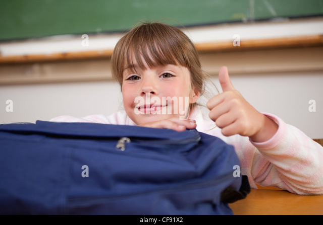 Cute schoolgirl posing with a bag and the thumb up - Stock Image
