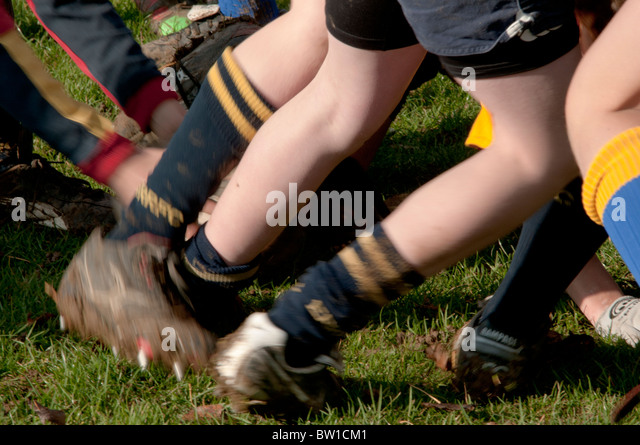 young boys playing rugby in a scrum in an outdoor playing field in autumn - Stock Image