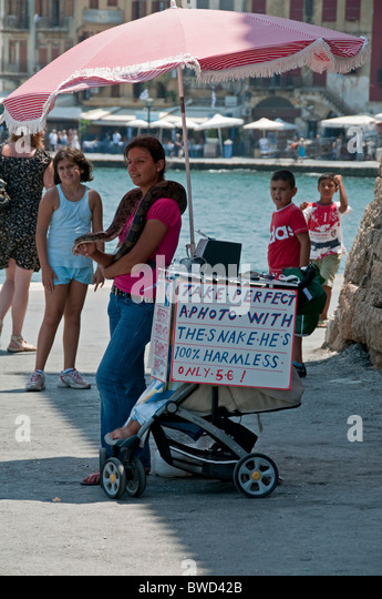 Street vendor using live snake as photographic prop. Chania, Crete, Greece. - Stock-Bilder