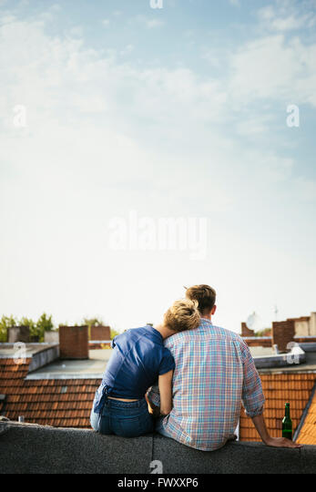 Germany, Berlin, Young couple sitting on rooftop with beer - Stock-Bilder