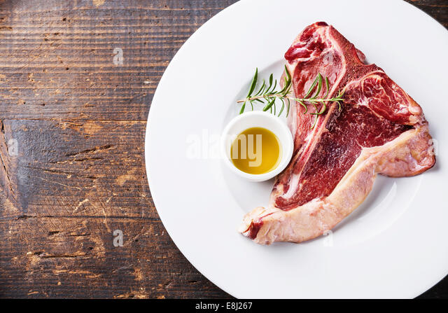 Raw fresh meat T-Bone Steak with rosemary and olive oil on white plate on dark wooden background - Stock-Bilder