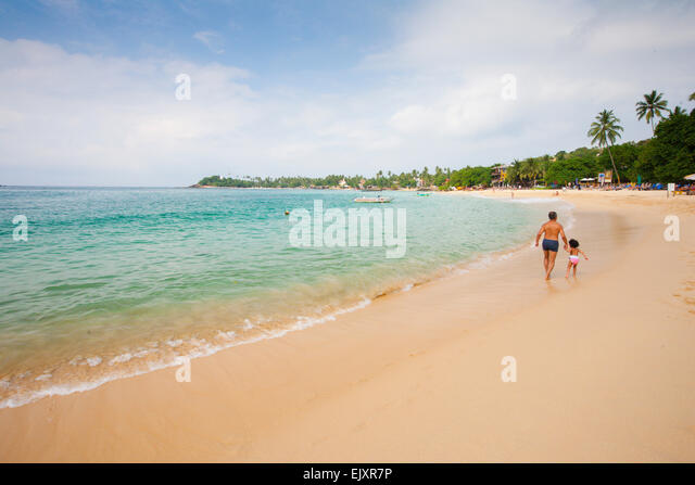 FATHER AND DAUGHTER WALKING ON UNAWATUNA BEACH - Stock Image