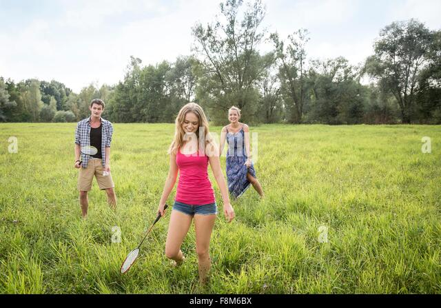 Group of young adults playing badminton in field - Stock Image