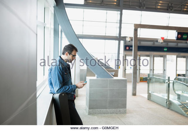 Man checking cell phone at train station - Stock Image