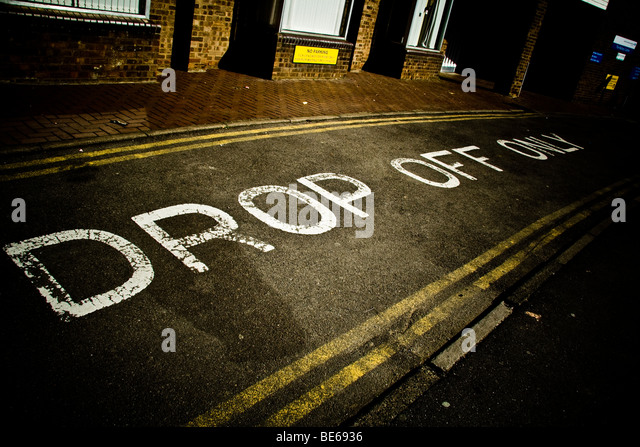 Drop off only written in paint on the road. - Stock Image