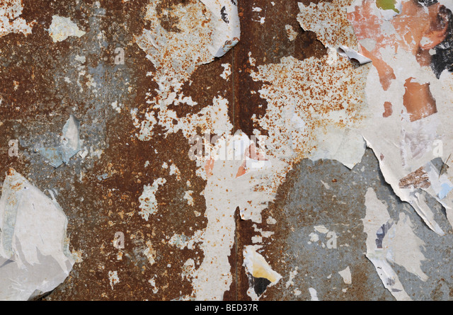 Corroded metal surface with remains of posters - Stock Image