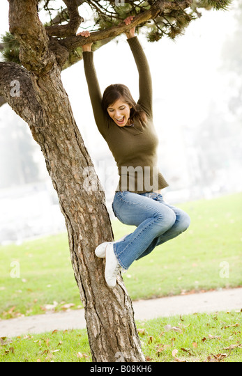 A woman jumping for joy, laughing, smiling in a park and playfully swinging from a tree limb. - Stock Image