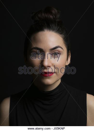 Portrait confident brunette woman against black background - Stock Image