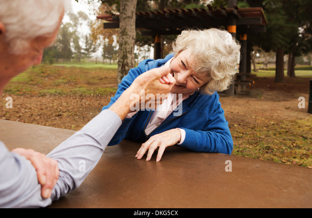 Husband and wife arm wrestling playfully - Stock Image