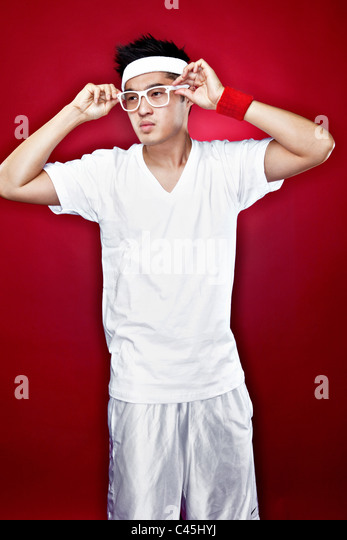 Studio 3/4 length portrait of Asian male teenager in white athletic gear putting on white nerdy glasses against - Stock Image
