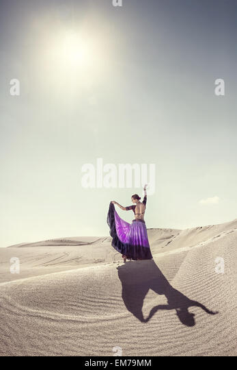 Woman in violet skirt dancing in the desert - Stock-Bilder