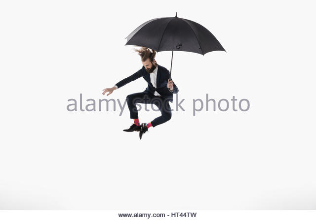 Businessman with umbrella jumping and clicking heels against white background - Stock-Bilder
