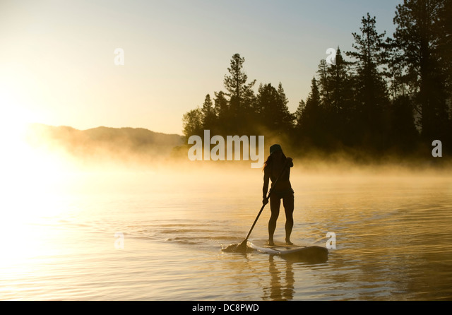 A woman, is silhouetted Stand Up Paddleboarding (SUP) at sunrise in the mist in Lake Tahoe, CA. - Stock-Bilder