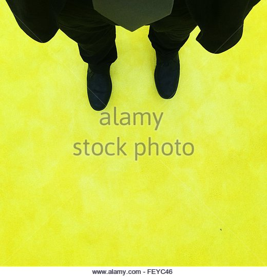 Low Section Of Man Standing On Yellow Floor - Stock Image
