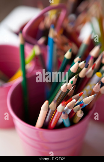 Close up high angle view of multicolor art colored pencils in pink bucket - Stock Image