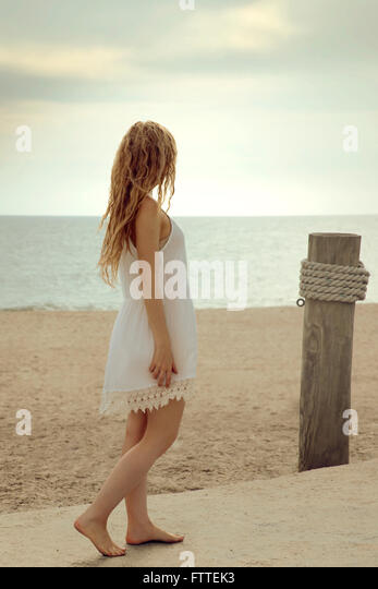 Blonde woman walking on beach - Stock Image