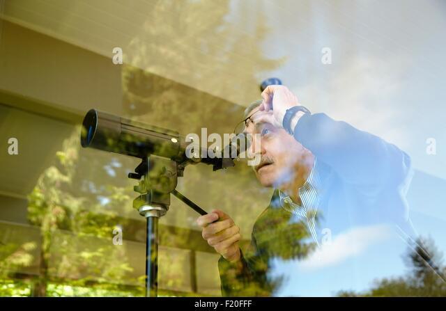 Senior man at home, using telescope through window - Stock-Bilder