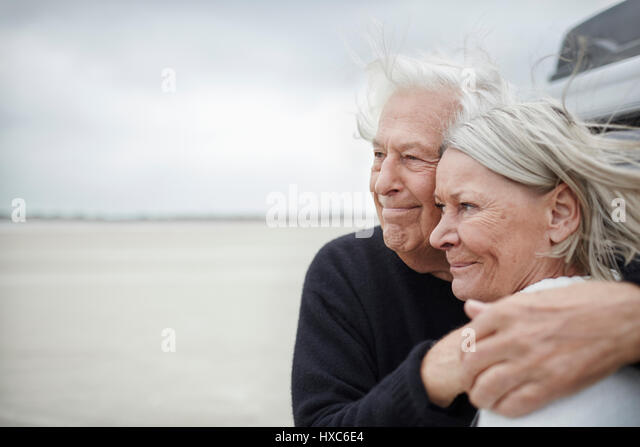 Affectionate senior couple hugging and looking away on beach - Stock Image