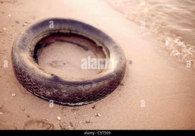 Germany, Old Tire on beach - Stock Image