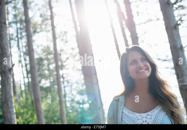 A woman enjoying a leisurely walk in a forest. - Stock Image