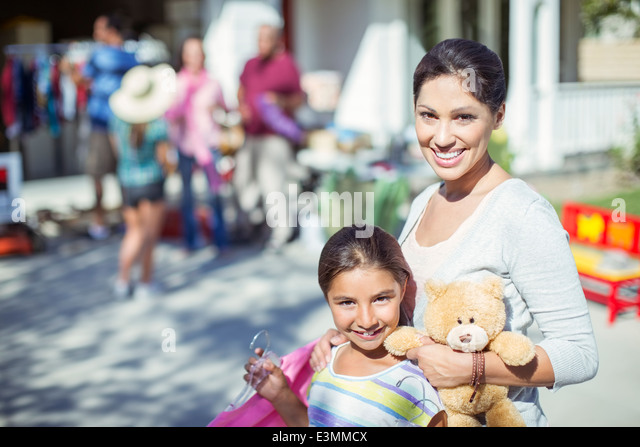 Portrait of mother and daughter shopping at yard sale - Stock Image