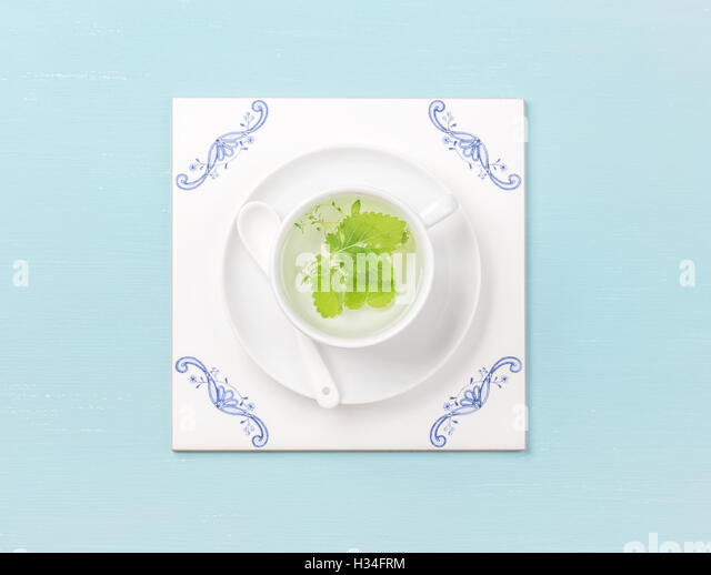 Cup of tea on white tile board over sky-blue background - Stock Image