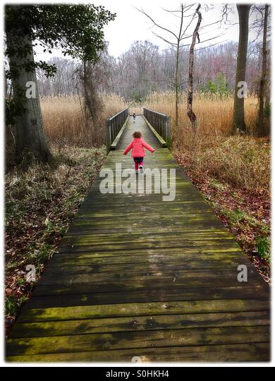Toddler running along a nature center walkway - Stock Image